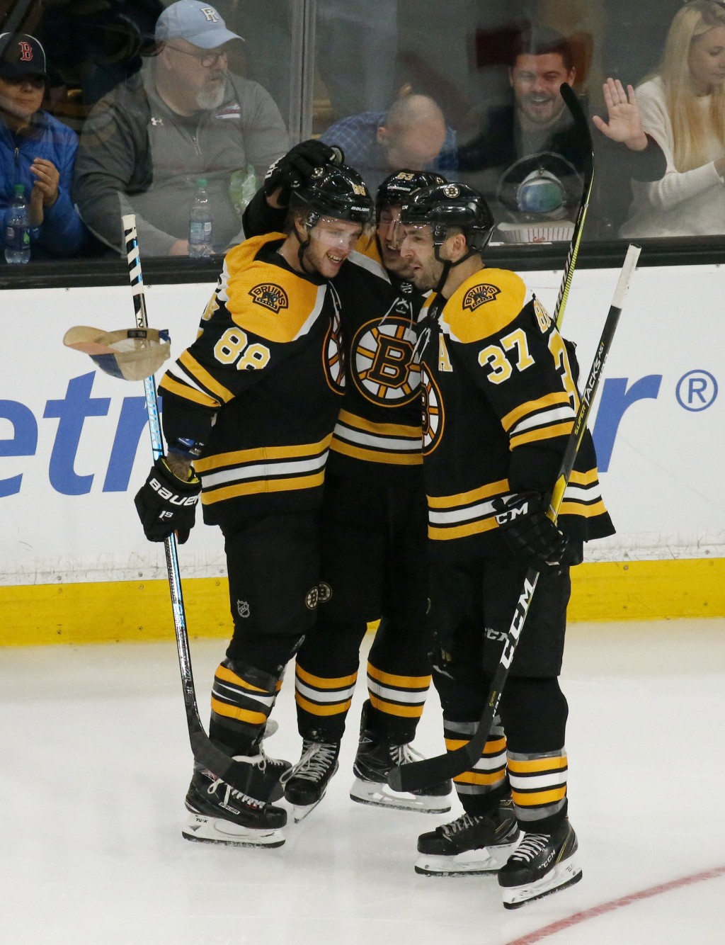 A cap falls past Boston Bruins right wing David Pastrnak (88) as he celebrates his third goal of an NHL hockey game with teammates Brad Marchand, cent
