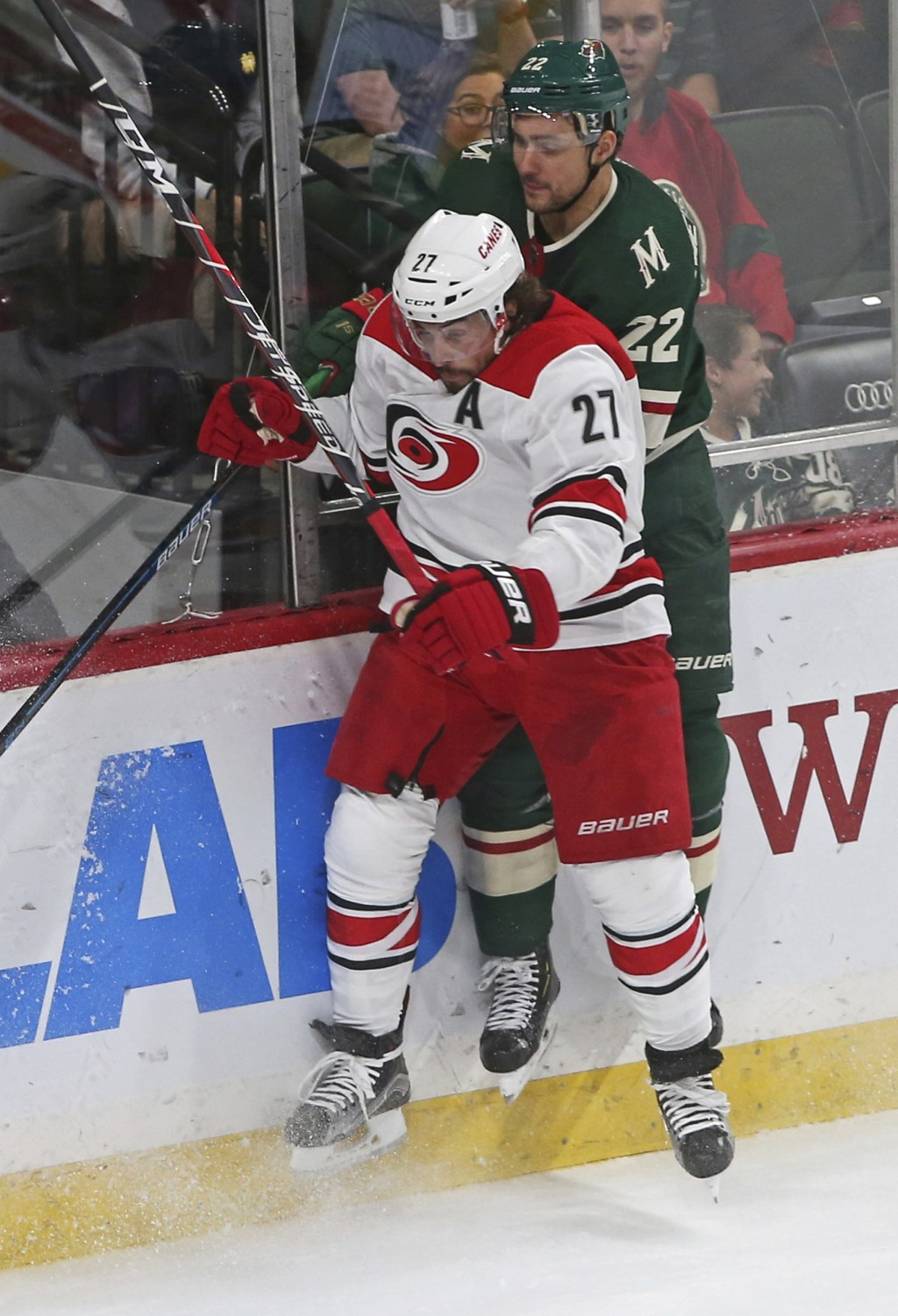 Carolina Hurricanes' Justin Faulk, left, and Minnesota Wild's Nino Niederreiter, of Switzerland, leave the ice in a check along the boards during the