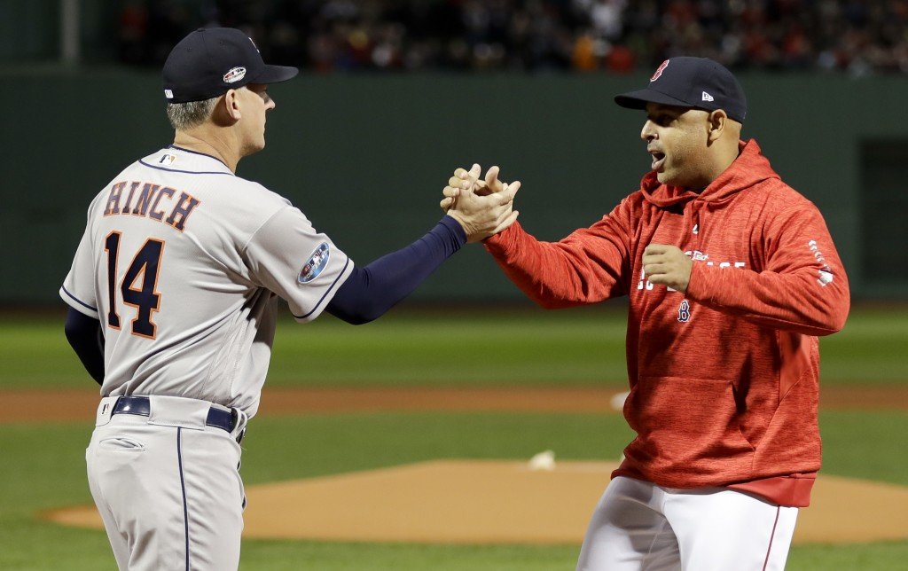 Houston Astros manager AJ Hinch, left, and Boston Red Sox manager Alex Cora shake Hanes before Game 1 of a baseball American League Championship Serie