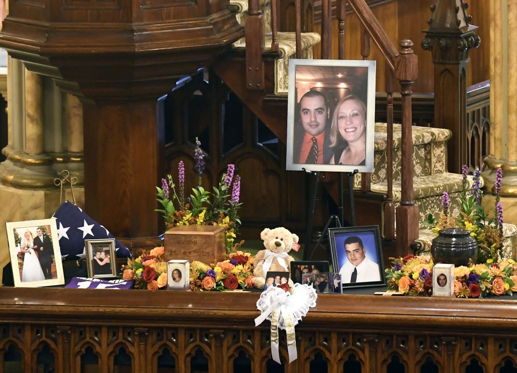 A unity urn with cremated ashes of Robert Joseph Dyson and Mary E. Dyson is set in place as friends and family prepare for a funeral mass atSt. Stani