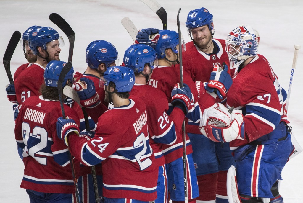 Players from the Montreal Canadiens celebrate after defeating the Pittsburgh Penguins in an NHL hockey game, Saturday, Oct. 13, 2018 in Montreal.  (Gr