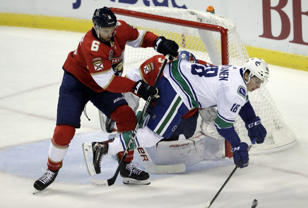 Vancouver Canucks right wing Jake Virtanen (18) falls to the ice as he goes for the puck against Florida Panthers defenseman Alexander Petrovic (6) du