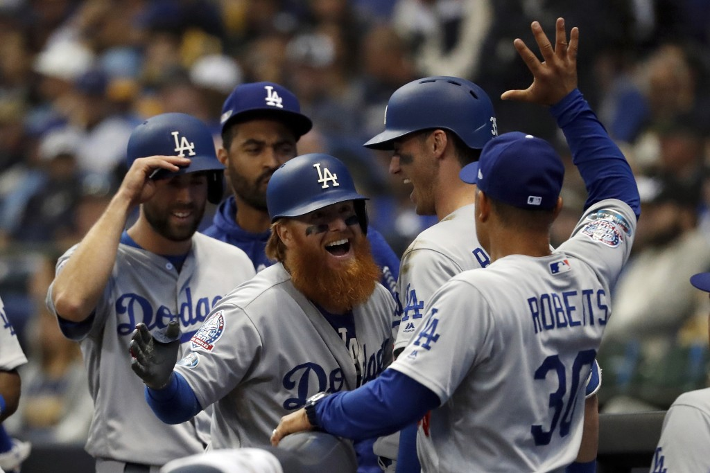 Los Angeles Dodgers' Justin Turner (10) celebrates with manager Dave Roberts (30) after hitting a two-run home run during the eighth inning of Game 2