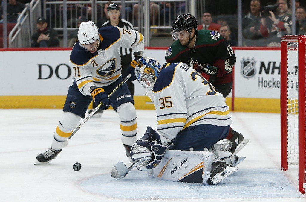 Buffalo Sabres goaltender Linus Ullmark (35) makes a save against Arizona Coyotes center Vinnie Hinostroza (13) as Evan Rodrigues tries to clear the p