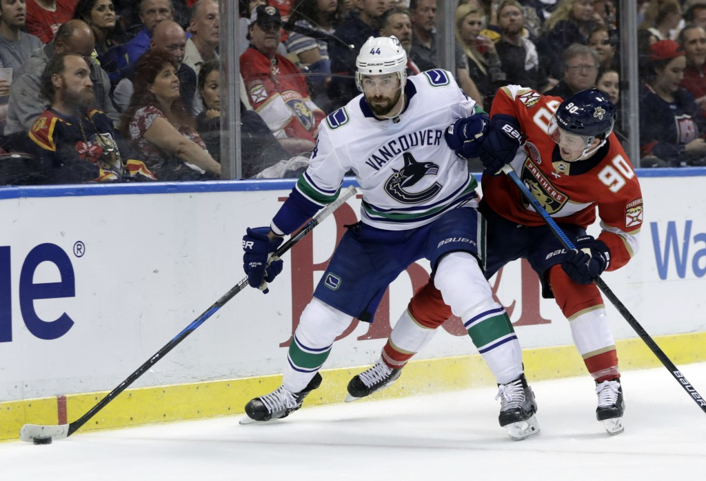Vancouver Canucks defenseman Erik Gudbranson (44) and Florida Panthers center Jared McCann (90) go for the puck during the second period of an NHL hoc