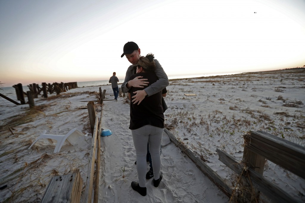 Matthew Fortner hugs his mother, Lavonia Fortner, as they walk to view the beach for what they feel is the last time, after they sifted through the ru