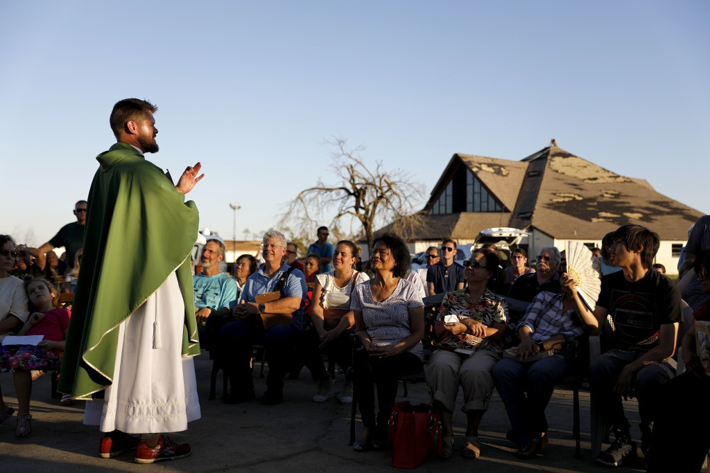 Father Michael Nixon holds Mass outside Saint Dominic Catholic Church which stands damaged in the background form hurricane Michael in Panama City, Fl
