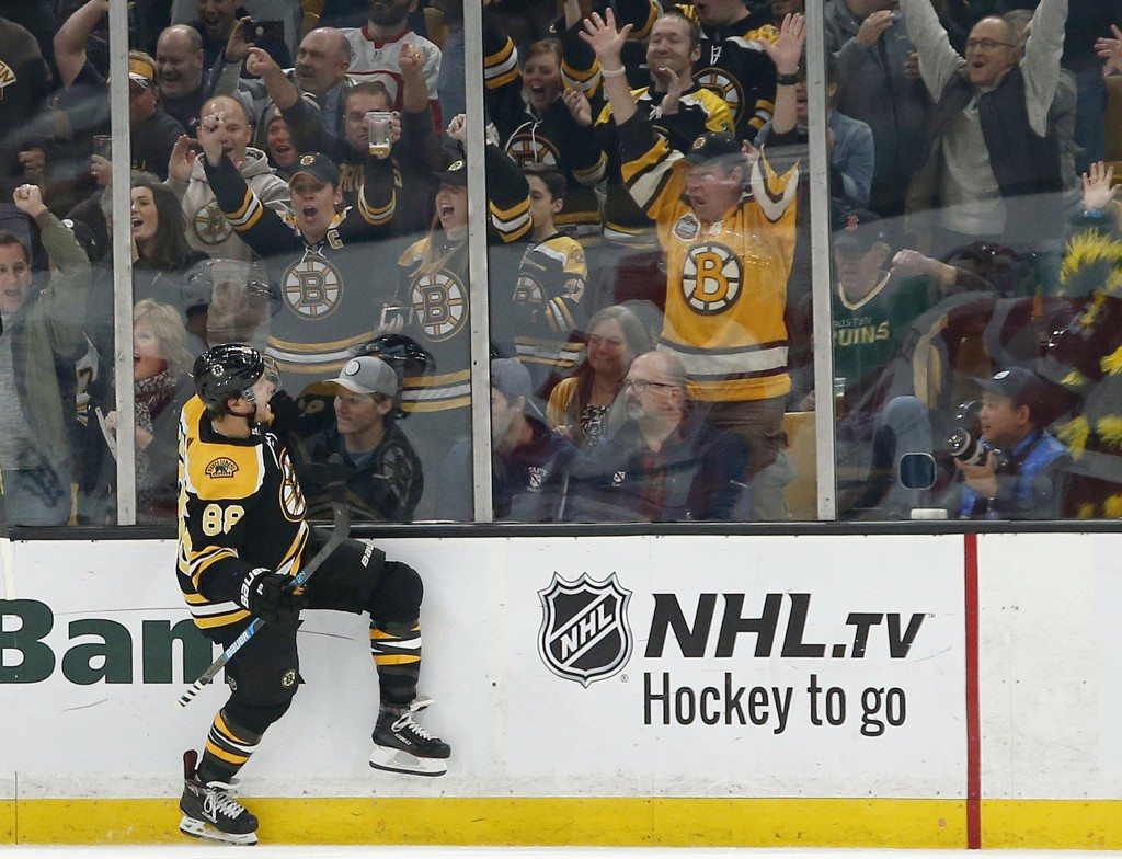 Boston Bruins right wing David Pastrnak (88) reacts after scoring during the first period of an NHL hockey game against the Detroit Red Wings, Saturda