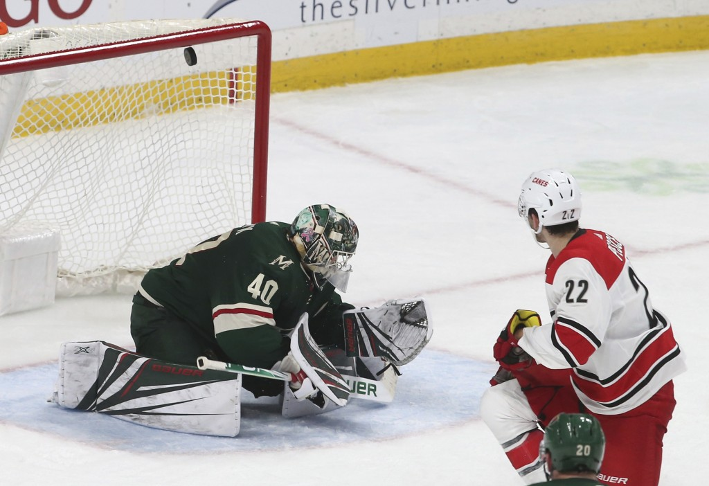 Carolina Hurricanes' Brett Pesce, right, sends a shot over Minnesota Wild goalie Devan Dubnyk for a goal during the second period of an NHL hockey gam