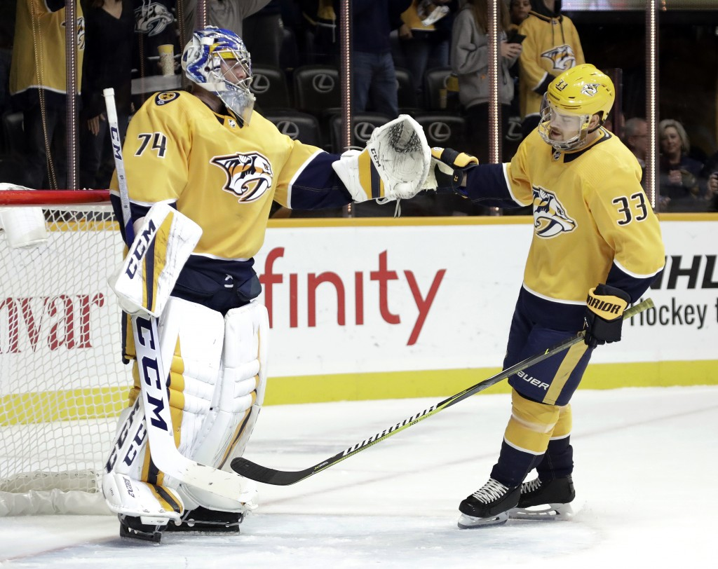 Nashville Predators left wing Viktor Arvidsson (33), of Sweden, slaps gloves with goaltender Juuse Saros (74), of Finland, after Arvidsson scored a go