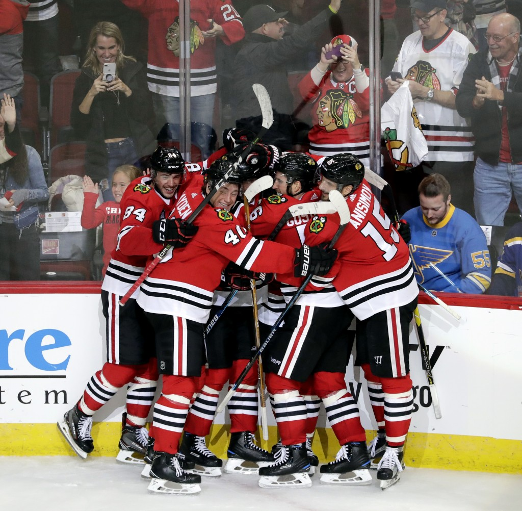 Chicago Blackhawks right wing Alex DeBrincat, center, celebrates with teammates after scoring in overtime against the St. Louis Blues during an NHL ho