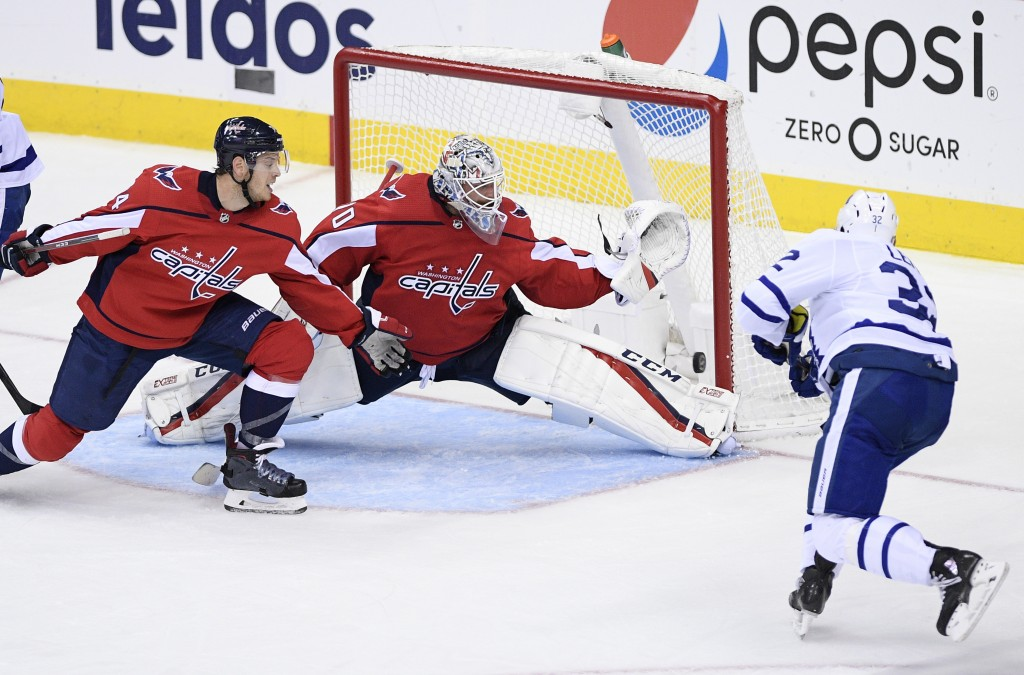 Toronto Maple Leafs left wing Josh Leivo (32) scores a goal past Washington Capitals goaltender Braden Holtby (70) and defenseman John Carlson, left,
