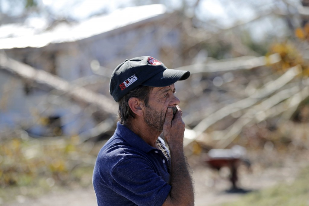In this Oct. 13, 2018 photo, Clinton Moseley who lives with his mother, reacts as he surveys a large tree that fell on the home in the aftermath of Hu...