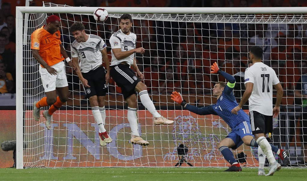 Netherland's Ryan Babel, Germany's Jonas Hector and Mats Hummels, from left, jump for the ball in front of Germany's keeper Manuel Neuer during the UE