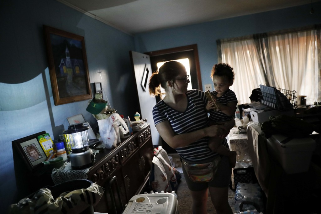 Rachel Hyatt holds her daughter, Eva, 2, in their damaged home as they prepare to spend a fifth night without power and running water in the aftermath...