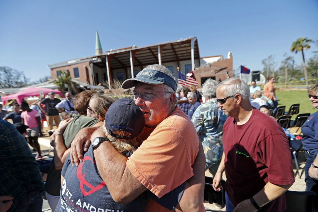 Jerry Register, a congregation member of St. Andrew United Methodist Church, hugs a fellow church member during Sunday service, outside the damaged ch...