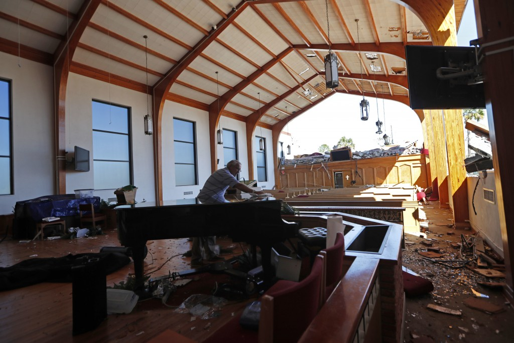 Charles Olmstead wipes off the grand piano that was spared damage, inside the heavily damaged St. Andrew United Methodist Church, while a Sunday servi...