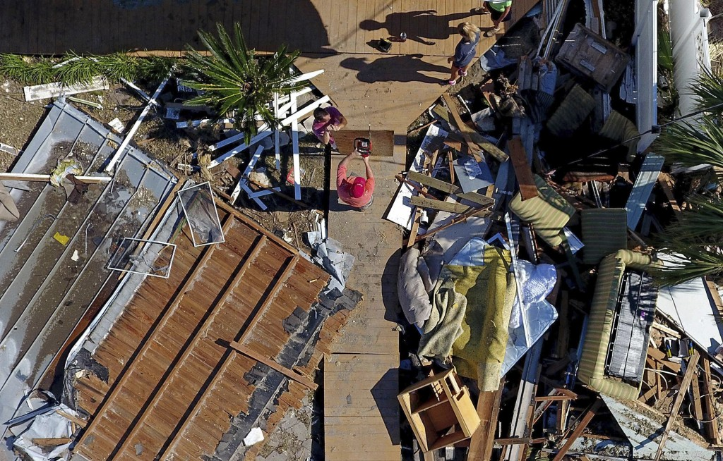 The Wood family begins cleanup efforts among the debris of their damaged home from hurricane Michael in Mexico Beach, Fla., Sunday, Oct. 14, 2018. (AP...