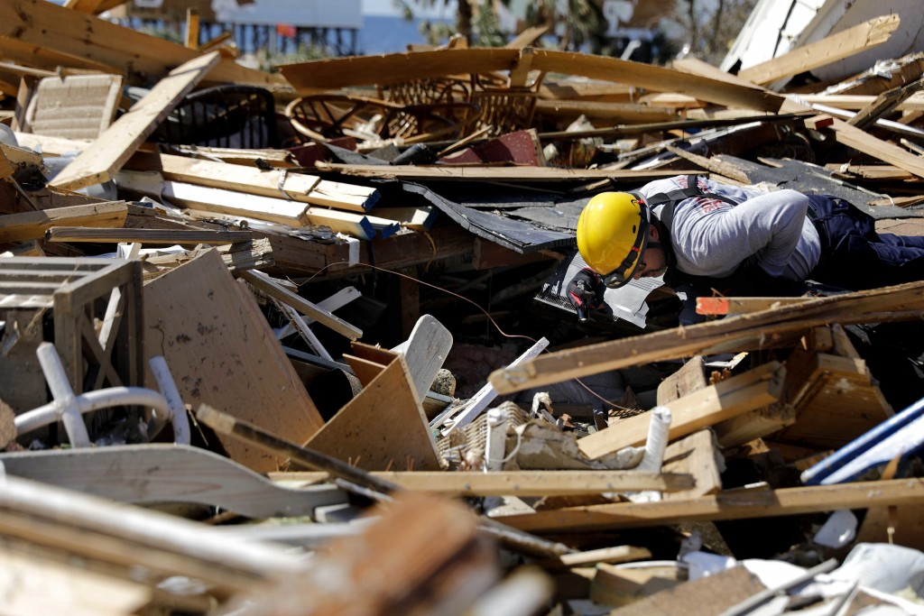 A member of a South Florida urban search and rescue team sifts through a debris pile for survivors of hurricane Michael in Mexico Beach, Fla., Sunday,...