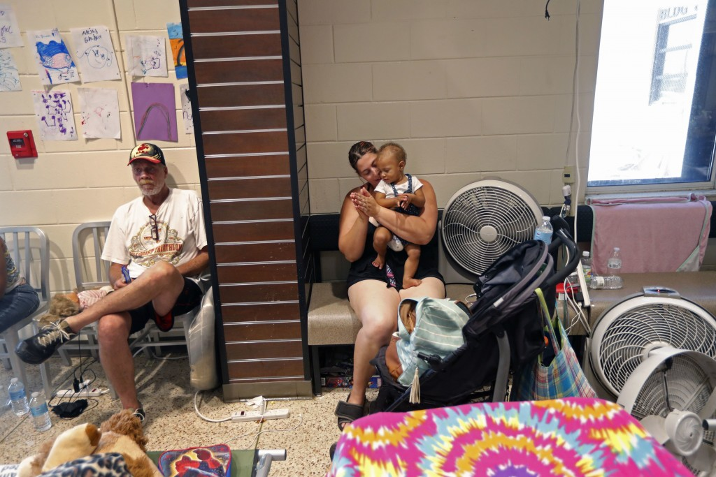 Terry Dominy, left, Sara Gray, and her baby Gabriella Horne, 8 months, all of of Springfield, Fla., sit inside an evacuation shelter at Rutherford Hig...
