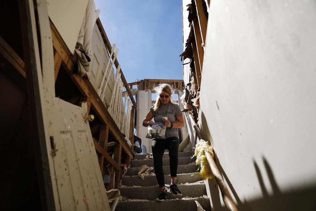 """Candace Phillips retrieves personal items from her damaged home in Mexico Beach, Fla., Sunday, Oct. 14, 2018, in the aftermath of Hurricane Michael. """"..."""