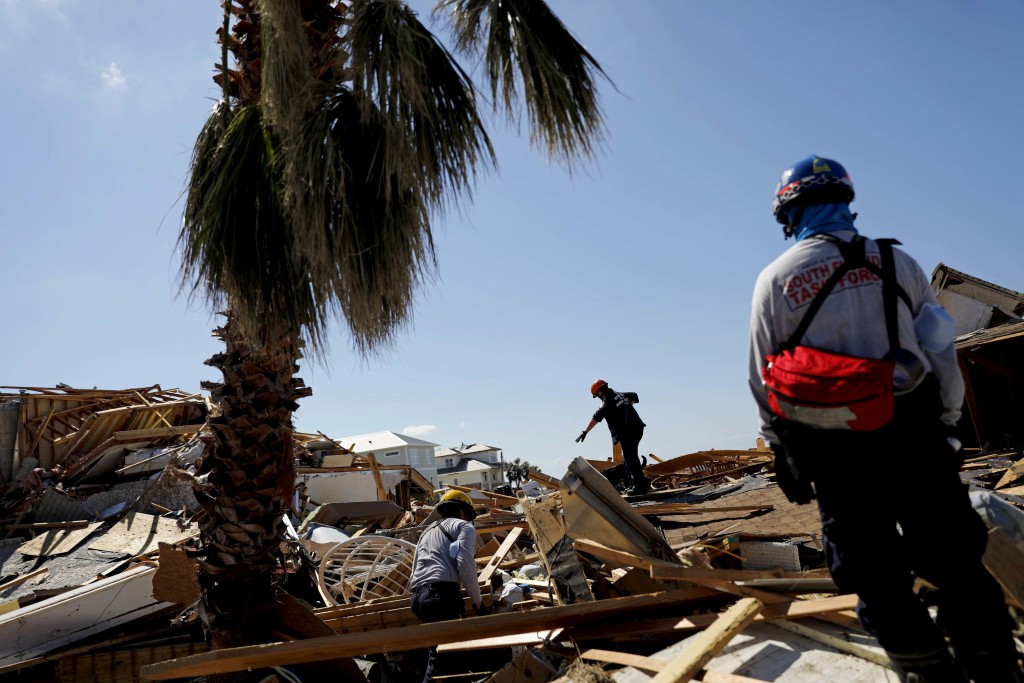 Members of a South Florida urban search and rescue team sift through a debris pile for survivors of Hurricane Michael in Mexico Beach, Fla., Sunday, O...