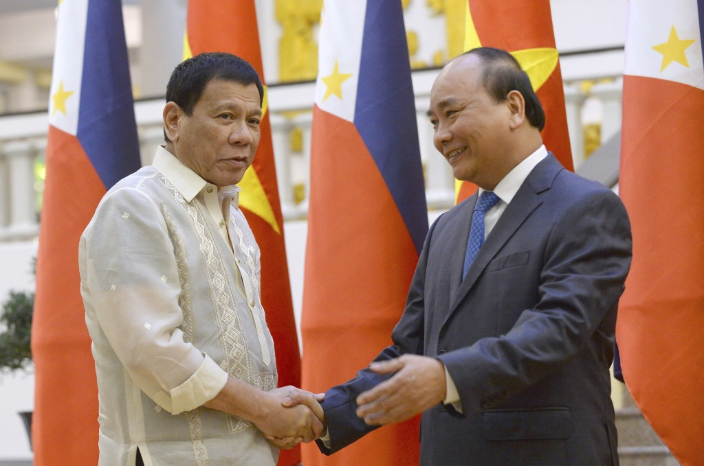 FILE - In this Sept. 29, 2016, file photo, Philippine President Rodrigo Duterte, left, shakes hands with Vietnamese Prime Minister Nguyen Xuan Phuc as...
