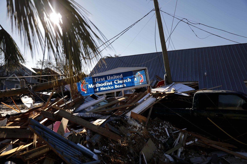 A sign for a damaged church sits among the debris from hurricane Michael in Mexico Beach, Fla., Sunday, Oct. 14, 2018. (AP Photo/David Goldman)