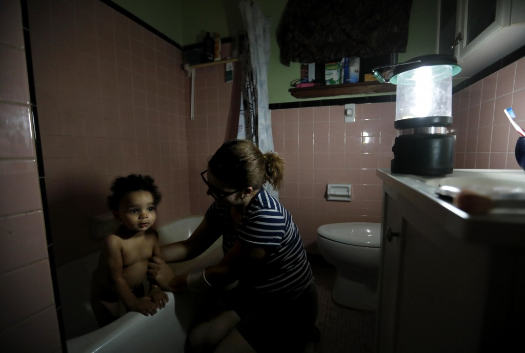 Rachel Hyatt bathes her daughter, Eva, 2, using a lantern and bottled water in their damaged home as they spend a fifth night without power and runnin...
