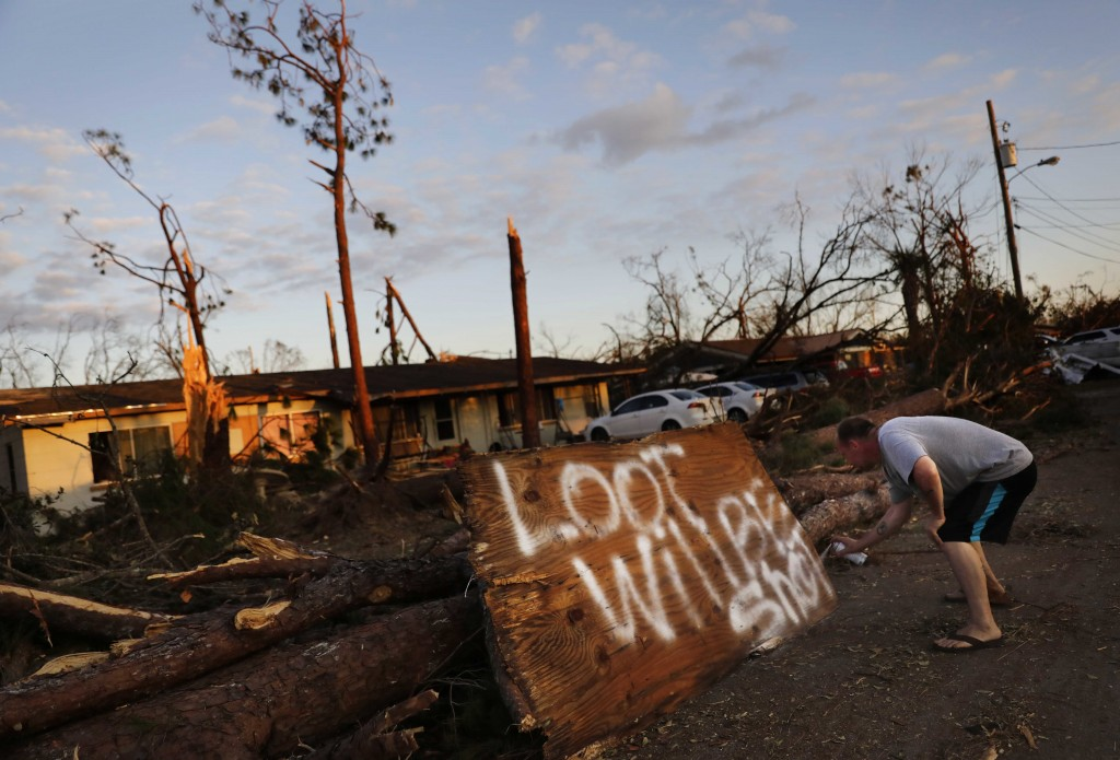 Ron Hyatt spray paints a message to warn off looters outside his damaged home from Hurricane Michael in Callaway, Fla., Sunday, Oct. 14, 2018. (AP Pho...