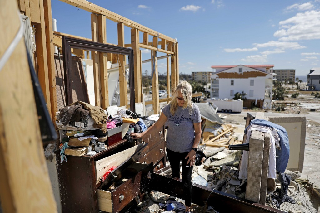 Candace Phillips sifts through what was her third-floor bedroom while returning to her damaged home in Mexico Beach, Fla., Sunday, Oct. 14, 2018, in t...