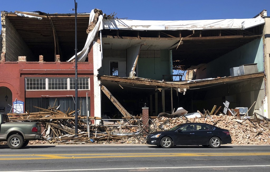 Cars sit in traffic outside buildings that lost their facades during Hurricane Michael on Sunday, Oct. 14, 2018, in Marianna, Fla. (AP Photo/Brendan F...