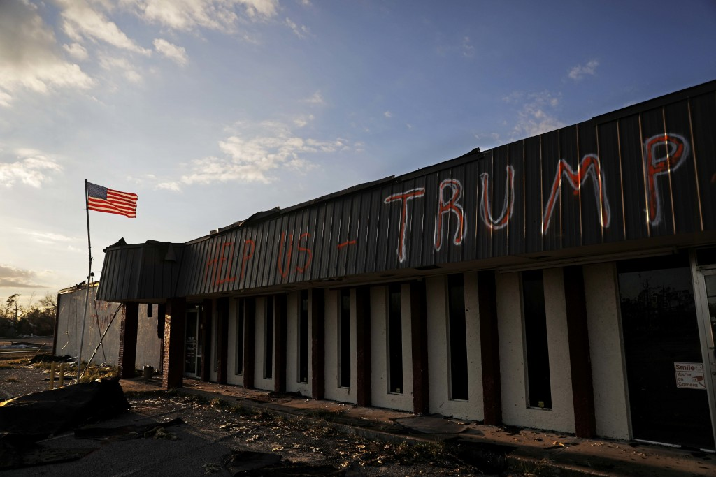 """A message reading """"Help us Trump"""" is written on a damaged business from Hurricane Michael in Callaway, Fla., Sunday, Oct. 14, 2018. (AP Photo/David Go..."""