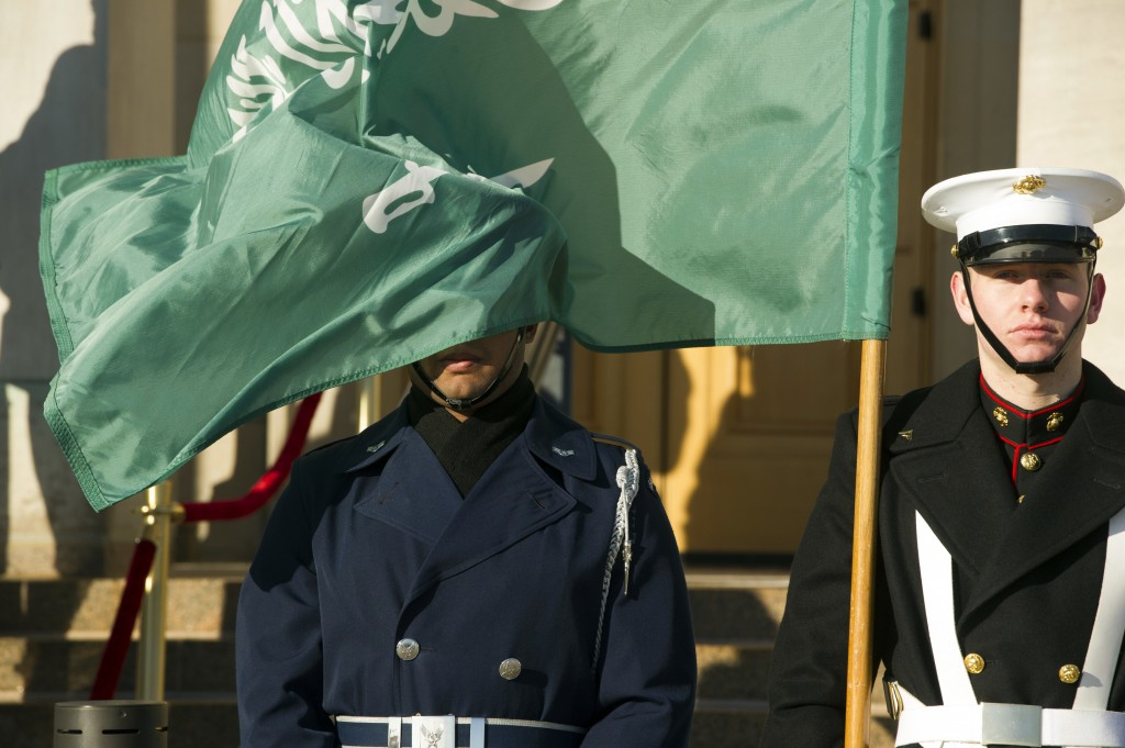 FILE - In this March 22, 2018 file photo, an honor guard member is covered by the flag of Saudi Arabia as Defense Secretary Jim Mattis welcomes Saudi