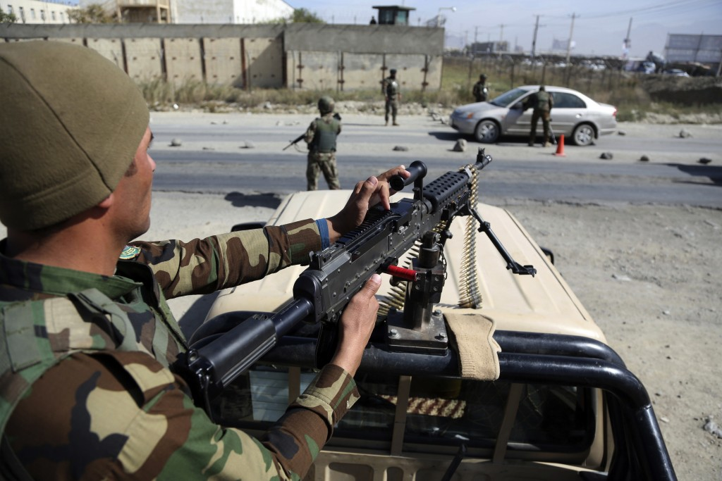 Afghan National army soldiers search a car at a checkpoint ahead of parliamentary elections scheduled for Oct. 20, at the Independent Election Commiss...