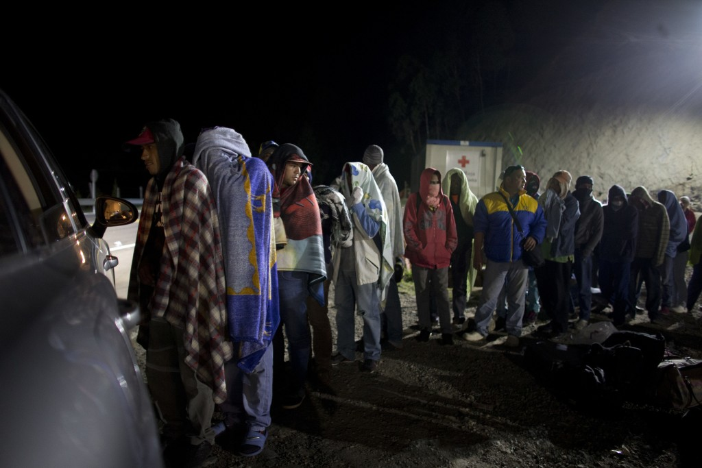 In this Aug. 31, 2018 photo, Venezuelan migrants line up for free bread and coffee, donated by a Colombian family from their car, at a gas station in