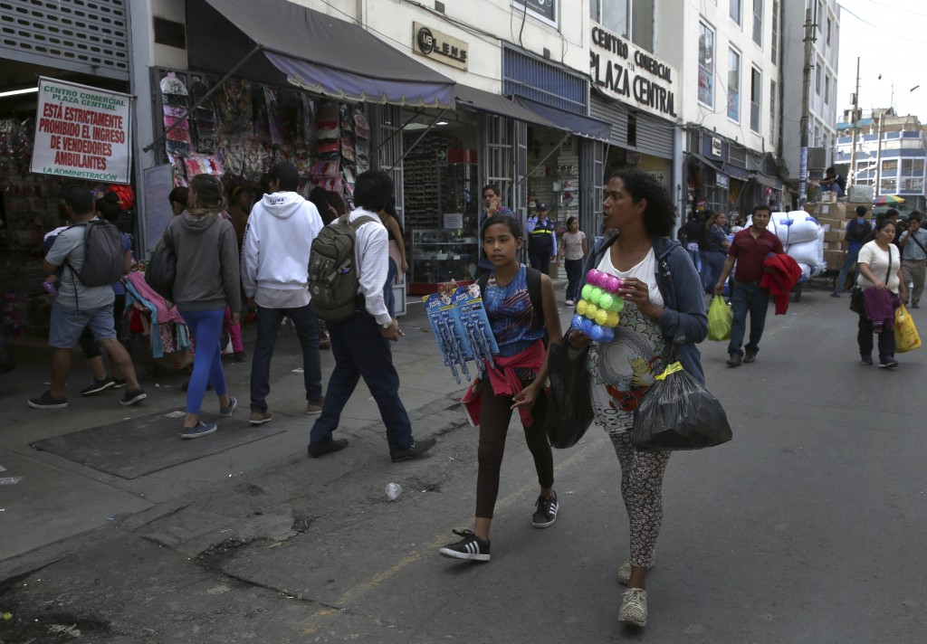 In this Oct. 9, 2018 photo, Venezuelan Sandra Cadiz and her 10-year-old daughter Angelis walk try to sell cotton swabs and razors near the Central Mar...