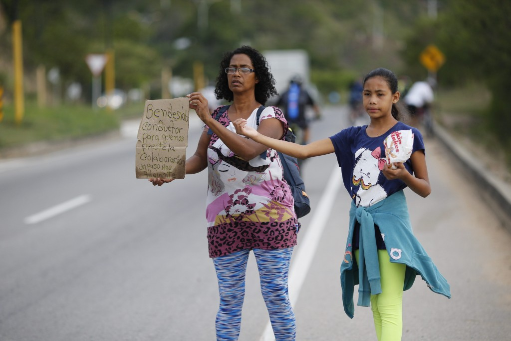 """In this Sept. 2, 2018 photo, Venezuelan Sandra Cadiz holds up her handmade sign carrying the Spanish message: """"Blessed driver, please help us with a r..."""