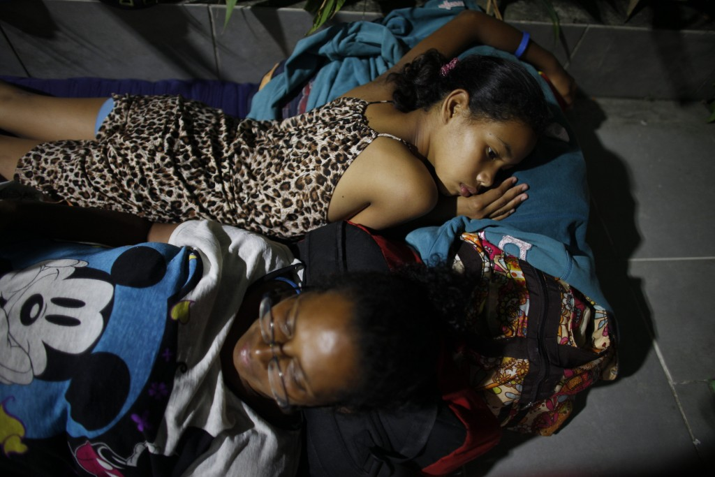 In this Sept. 3, 2018 photo, Venezuelan Sandra Cadiz and her 10-year-old daughter Angelis, lie on the floor of a gas station where they spent the nigh...