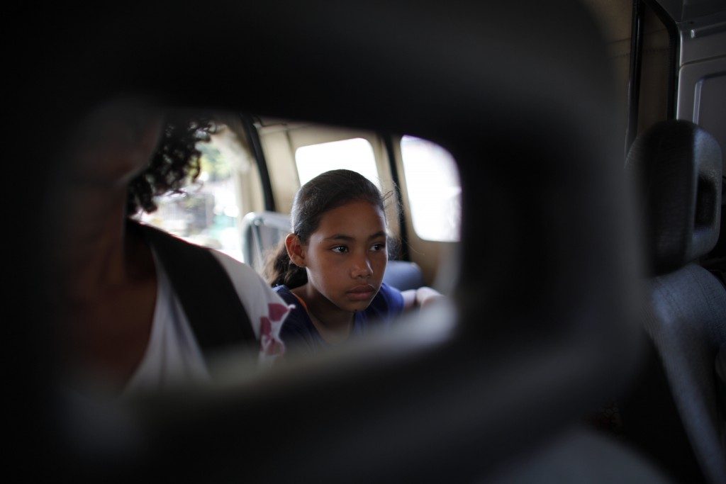 In this Sept. 2, 2018 photo, 10-year-old Venezuelan Angelis sits in a car with her mother Sandra Cadiz as they get a free ride from a driver to the ne