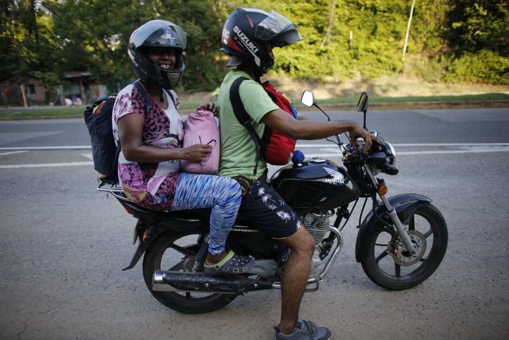 In this Sept. 2, 2018 photo, Venezuelan Sandra Cadiz gets a free ride from a motorcyclist to Peroles, Colombia, on her journey to Peru. The driver the