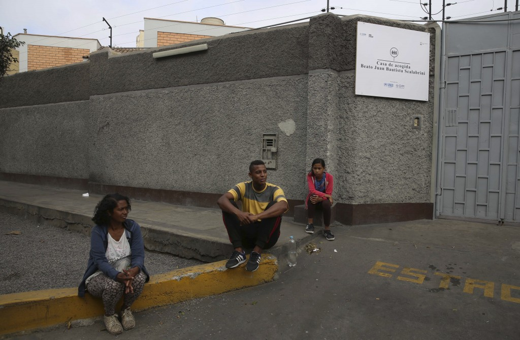 In this Oct. 9, 2018 photo, Venezuelan Sandra Cadiz, left, and her 10-year-old daughter Angelis sit with a fellow Venezuelan outside the Beato Juan Ba