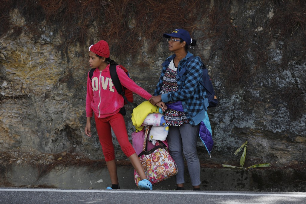 In this Sept. 1, 2018 photo, Venezuelan Sandra Cadiz holds the hand of her 10-year-old daughter, who's scared of the trucks racing by, as they wait fo...