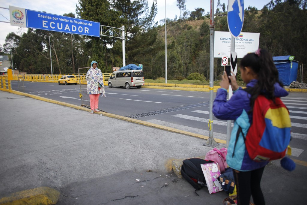 In this Sept. 5, 2018 photo, 10-year-old Venezuelan Angelis takes a picture of her mother Sandra Cadiz after they crossed the Colombian border into Hu