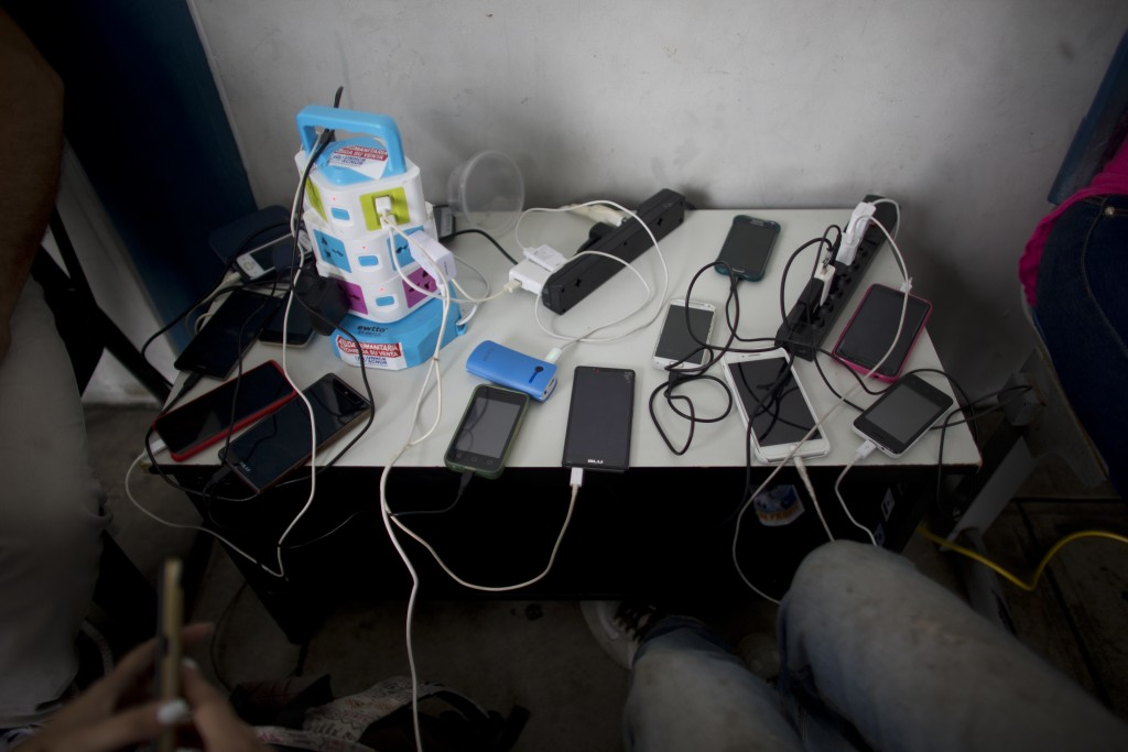 In this photo Sept. 7, 2018 photo, cellphones belonging to Venezuelans are charged for free at the immigration office in Aguas Verdes, Peru. It's not