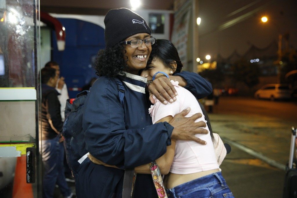 In this Sept. 8, 2018 photo, Venezuelan Sandra Cadiz, left, embraces her daughter-in-law Daniela Gomez as she arrives at the bus station in Lima, Peru