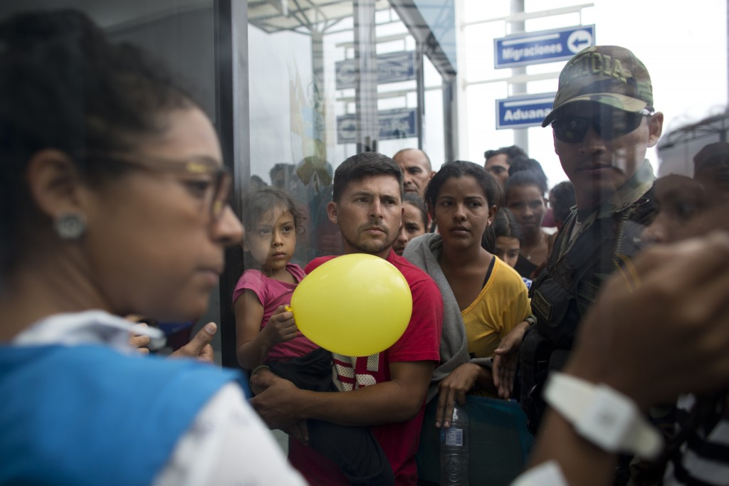 In this Sept. 6, 2018 photo, Venezuelans wait in line to be attended by Peruvian immigration officials in hopes of entering the country, in Tumbes, Pe