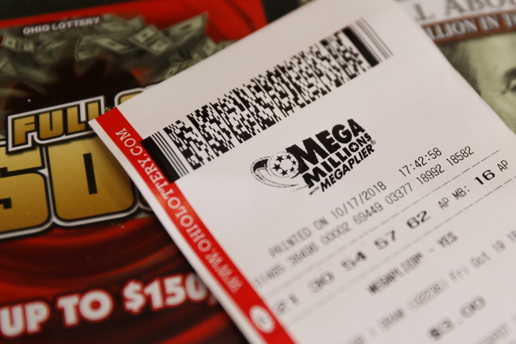 A Mega Millions lottery ticket rests on the shop counter at the Street Corner Market, Wednesday, Oct. 17, 2018, in Cincinnati. The estimated jackpot f...