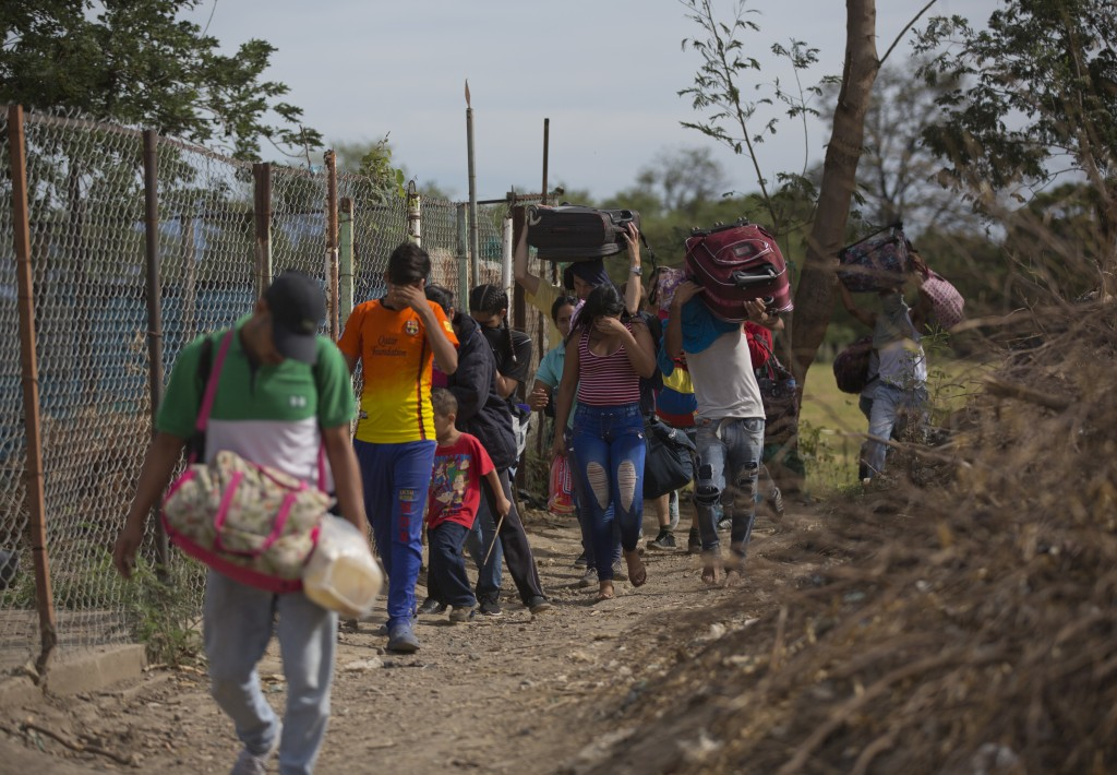 """In this Aug. 31, 2018 photo, Venezuelans illegally cross into Colombia, to Villa del Rosario, along a path known as a """"trocha."""" Uncontrolled by Venezu..."""
