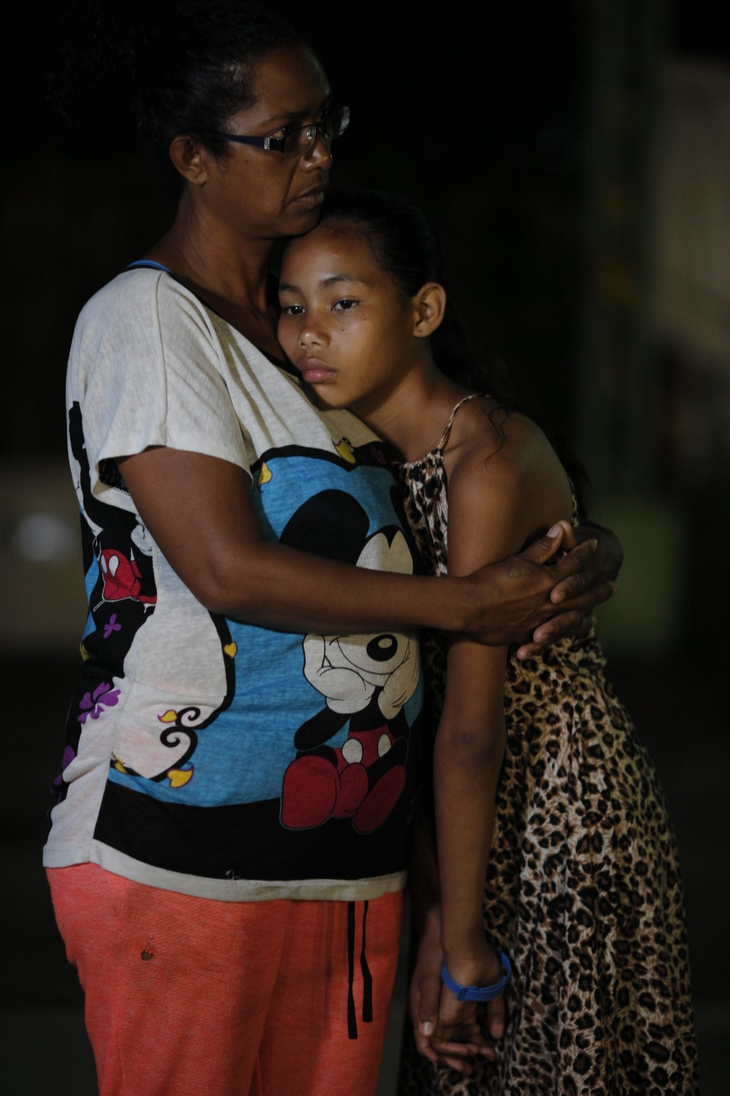 In this Sept. 4, 2018 photo, Venezuelan Sandra Cadiz and her 10-year-old daughter Angelis embrace after spending the night outside a Biomax gas statio